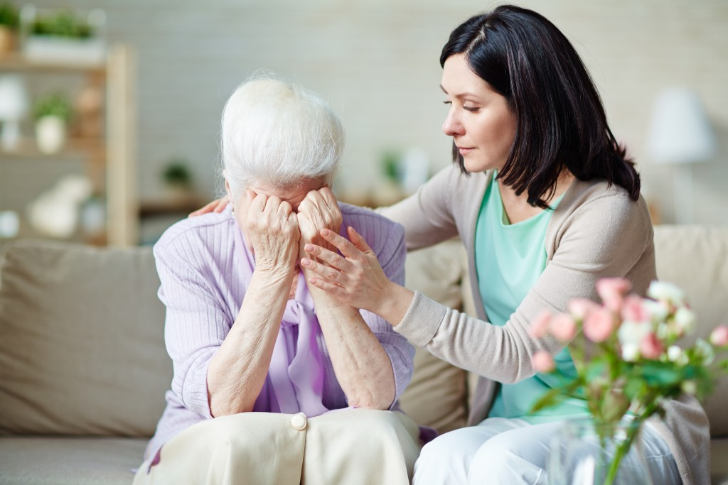 Depressed elderly women being consoled