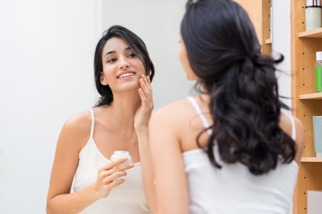 Woman putting moisturizing cream