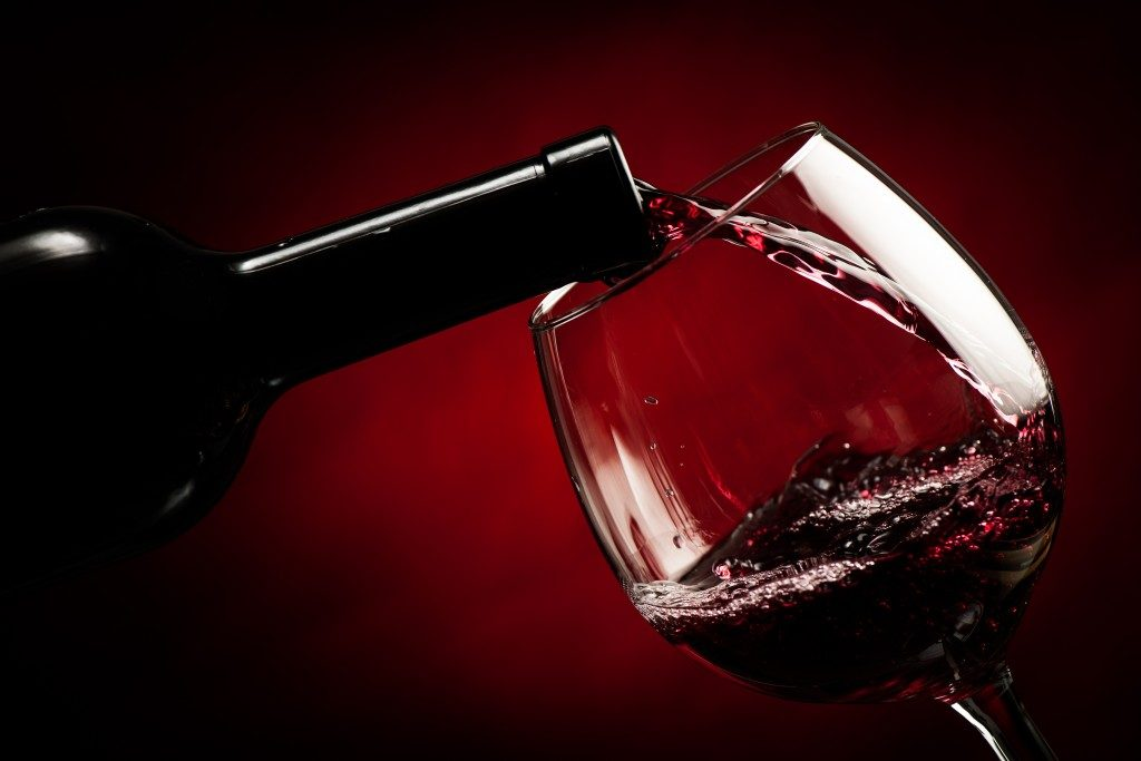 Close up of bottle of wine being poured in a glass