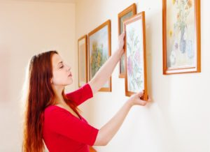 woman hanging picture frames