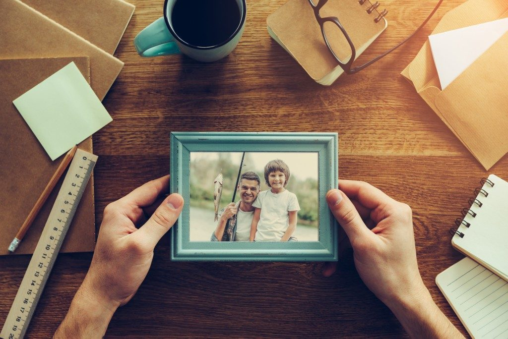 someone holding a photo of a father and son