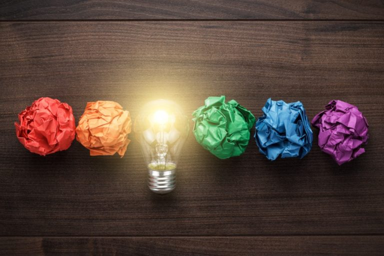 colorful crumpled papers with light bulb in the middle