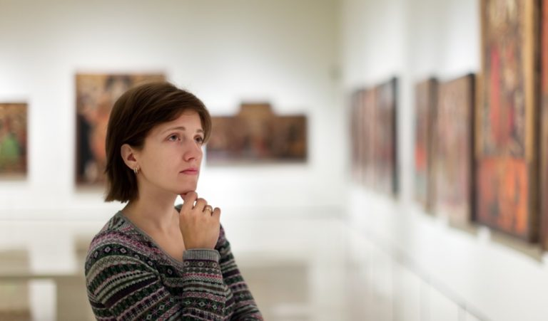 Woman looking at paintings