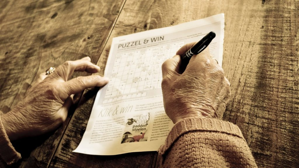 Old person answering a crossword puzzle