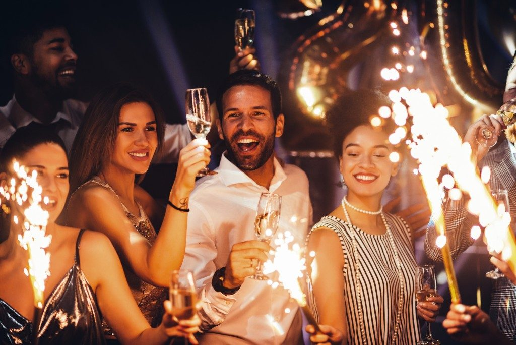 Group of friends holding sparklers and drinks