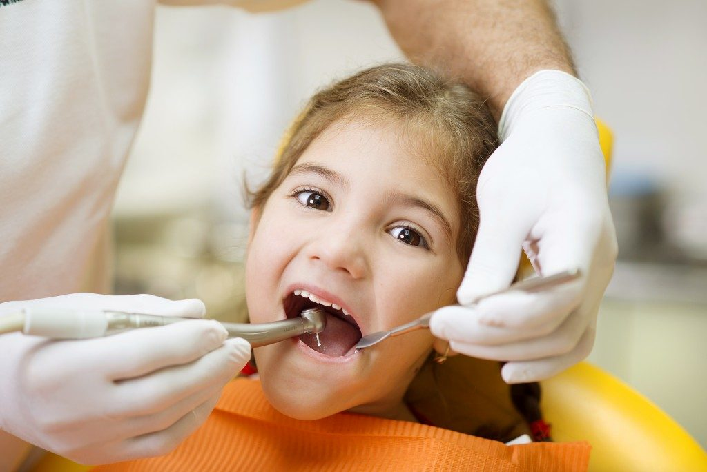 Dentist cleaning child's teeth
