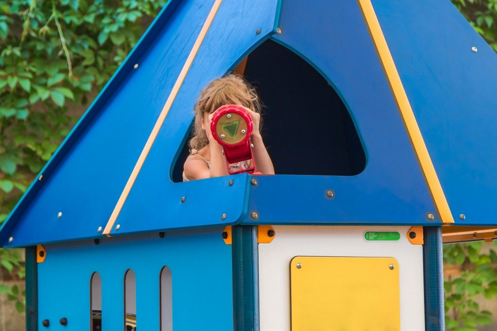 girl in the children's house, looking into the children's telescope, playground