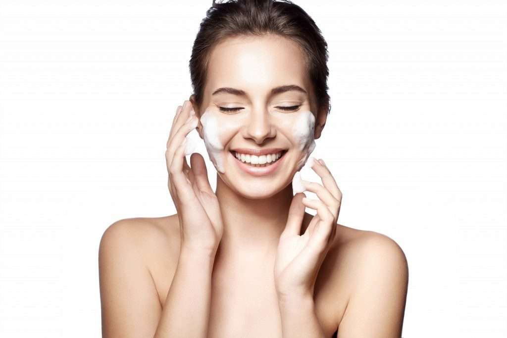 woman cleanses her face