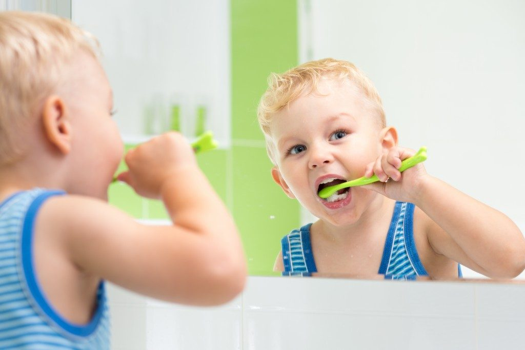 kid boy brushing teeth