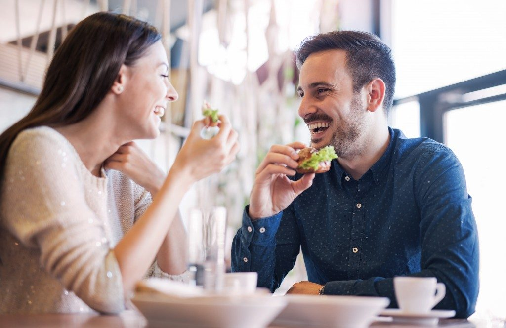couple eating sandwiches at a cafe