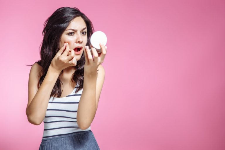 woman squeezing pimples while looking at the mirror