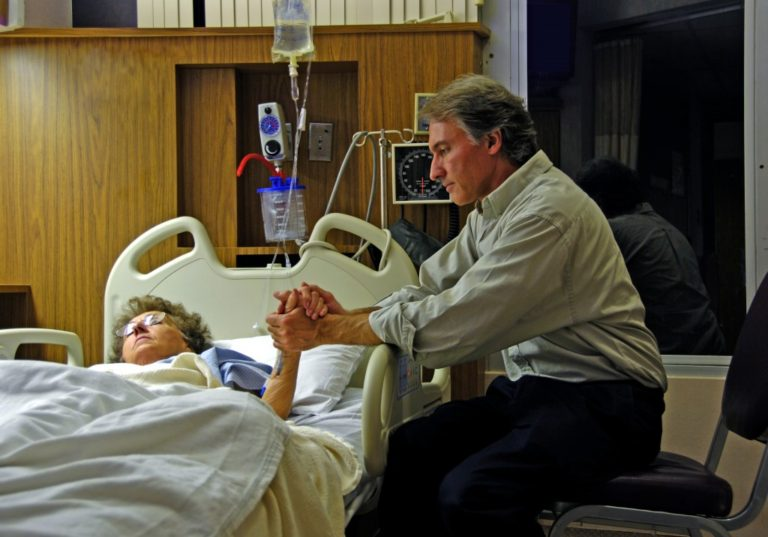 holding the hand of a sick loved one in a hospital bed
