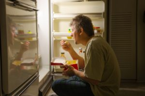 man eating in front of the fridge