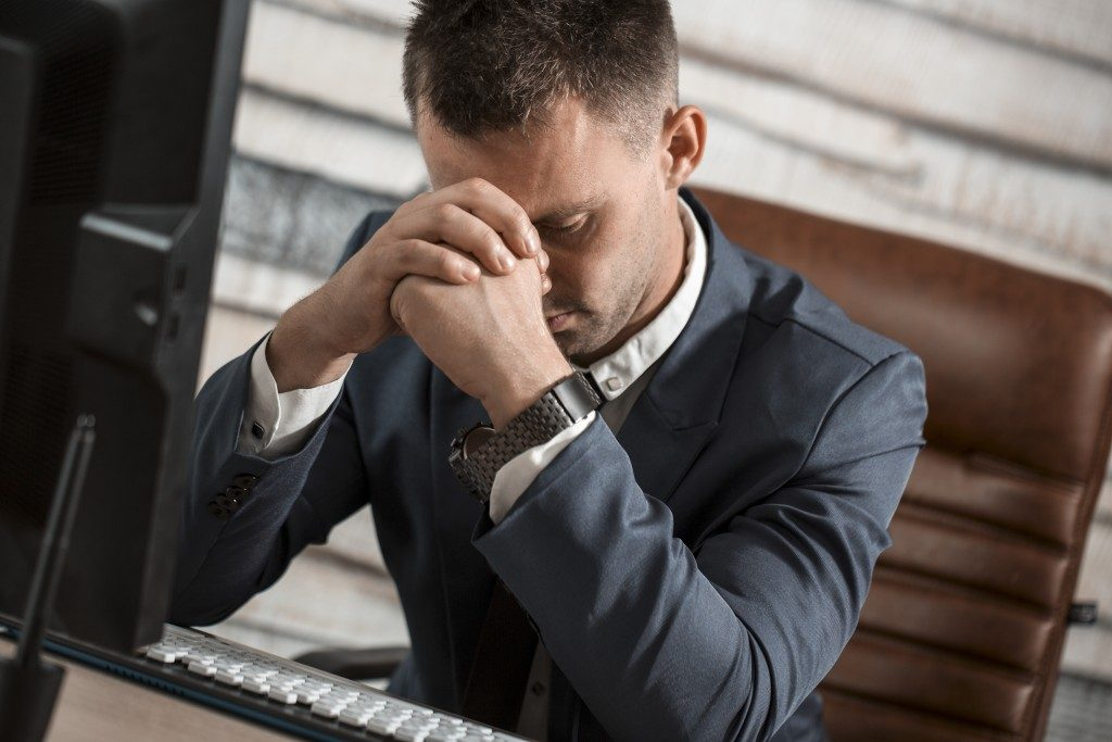 Man hunched over in front of computer