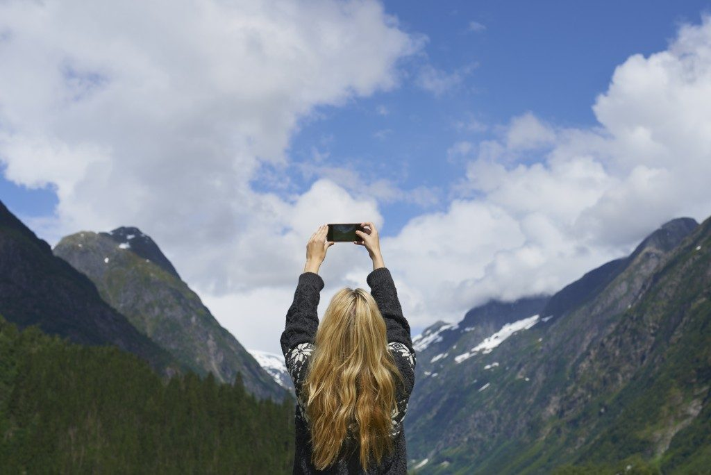 woman taking a photo of the scenery with phone