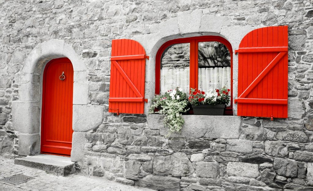 Old stone house with red wooden shutters and red door