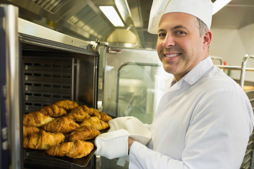 baker holding croissant