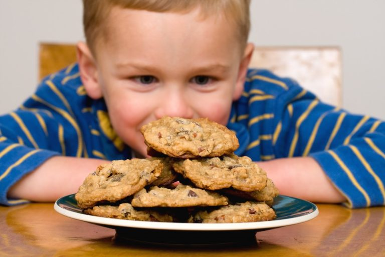 child staring at a plate of cookies